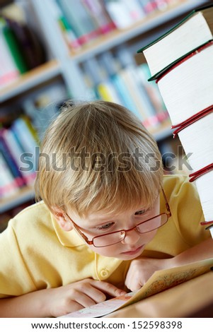 Portrait of surprised boy looking at map in library - stock photo
