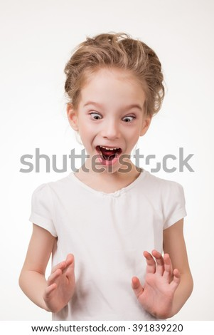 Portrait of surprised excited girl covering her mouth by the hand. Isolated on white background.