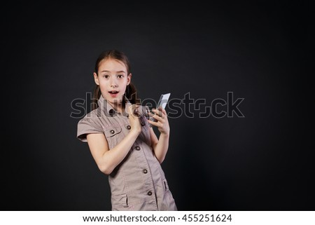 Portrait of surprised excited girl dial on touch screen of mobile phone at black background. Female child using internet in cell phone. New generation devices, communication - stock photo