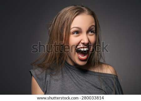 Portrait of surprised excited woman screaming amazed in shock. Beautiful girl isolated on grey background in casual grey wear. - stock photo