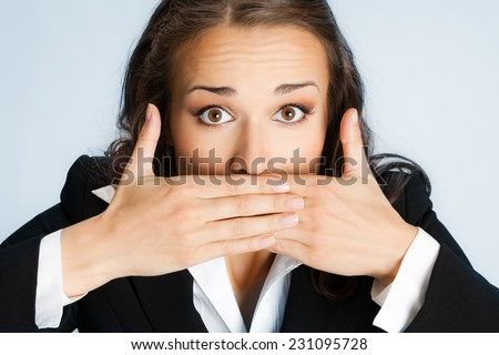 Portrait of surprised excited young business woman covering with hands her mouth, over blue background