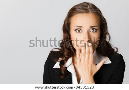 Portrait of surprised excited young business woman covering with hands her mouth, over grey background