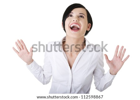 Portrait of surprised excited young business woman looking up, over grey background