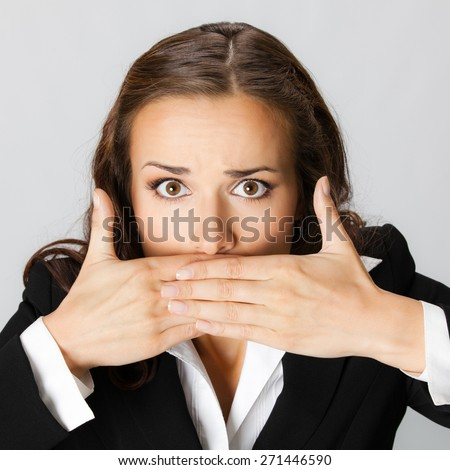 Portrait of surprised excited young businesswoman covering with hands her mouth, against grey background - stock photo