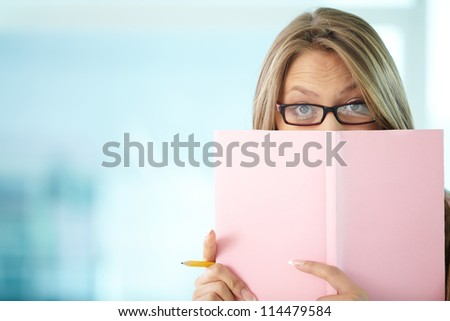 Portrait of surprised girl in eyeglasses peeping out of notepad - stock photo