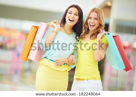 Portrait of surprised girls in smart casual with paperbags expressing astonishment - stock photo