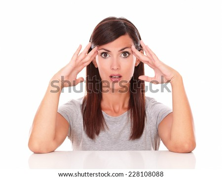 Portrait of surprised latin woman asking a question while looking at you on isolated studio - stock photo
