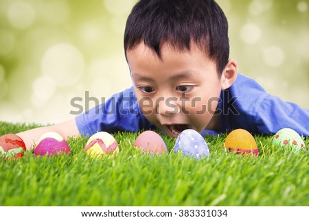 Portrait of surprised little boy lying on the grass and finding easter eggs, shot with bokeh background