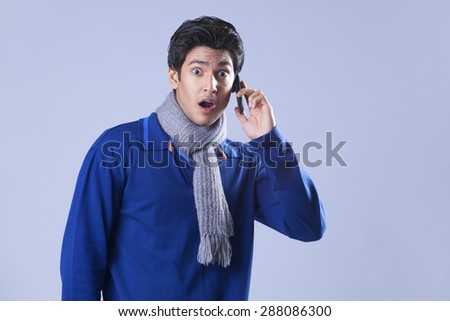 Portrait of surprised man having conversation on mobile phone