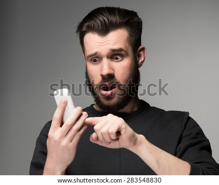 Portrait of surprised man talking on the phone on a gray background - stock photo