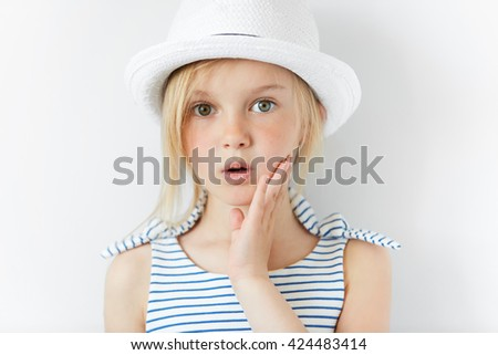 Portrait of surprised or frightened girl looking at the camera with a hand on her cheek. Close up shot of blonde Caucasian little girl with scared or shocked expression against white studio wall - stock photo