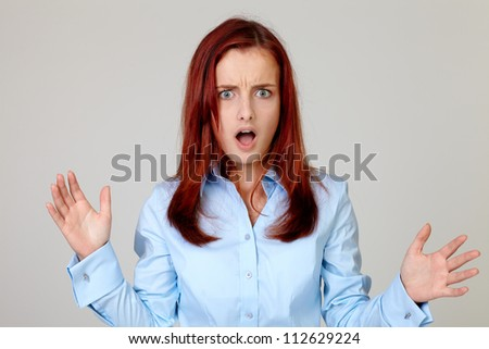 Portrait of surprised pretty businesswoman in blue shirt with hands, isolated on grey - stock photo