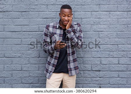 Portrait of surprised young african guy looking at cell phone while standing against a gray background - stock photo