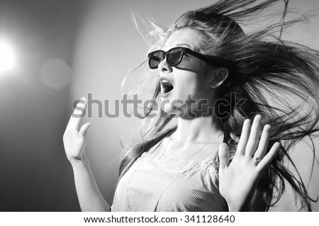 Portrait of surprised young beautiful lady in 3d glasses looking amazed. Black and white photography - stock photo