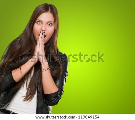 Portrait Of Surprised Young Woman against a green background - stock photo