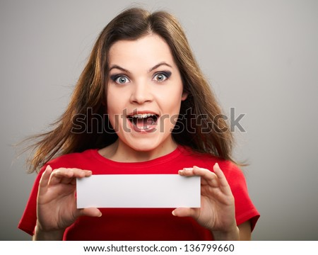 Portrait of surprised young woman in a red shirt. Woman holds a poster. On a gray background - stock photo