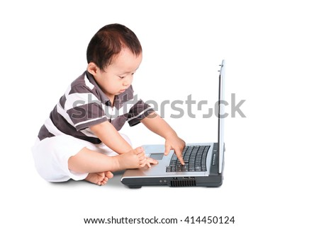 Portrait of sweet baby playing with a laptop computer while sitting in studio - stock photo