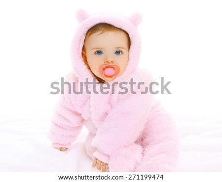 Portrait of sweet baby with pacifier in soft overalls on a white background - stock photo