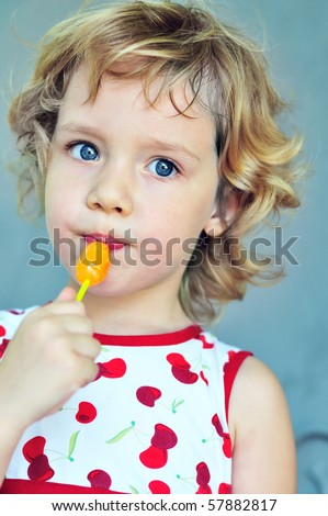 portrait of sweet blonde girl with lollipop - stock photo