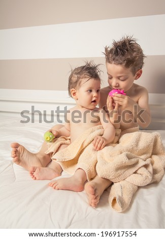 Portrait of sweet boy and little girl with wet hair under the towels playing over a bed after bath