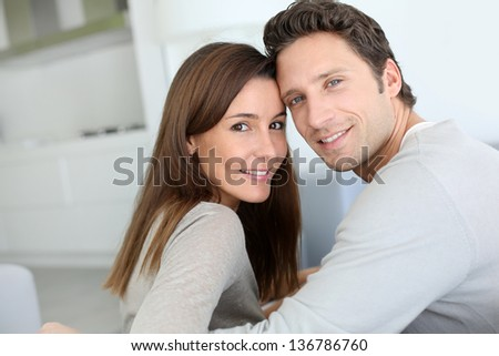Portrait of sweet couple sitting in sofa - stock photo