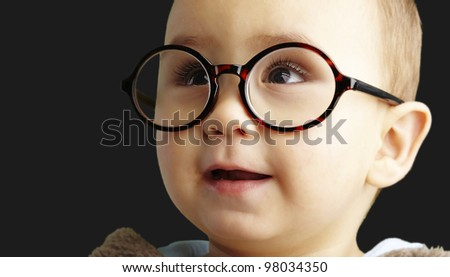 portrait of sweet kid wearing round glasses over black background - stock photo