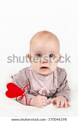 Portrait of sweet little baby girl holding red heart on a stick valentines day symbol.