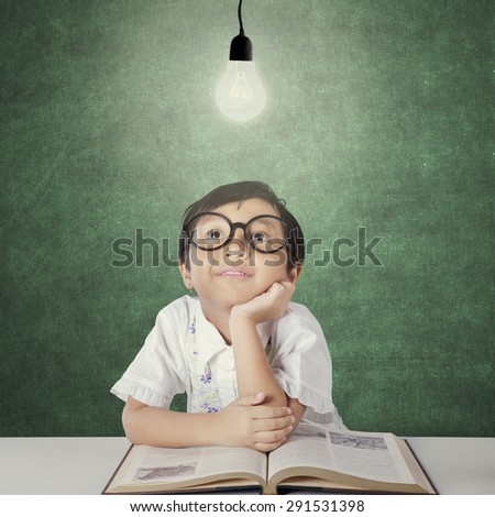 Portrait of sweet little girl sitting in the class while looking up at a bright lamp - stock photo