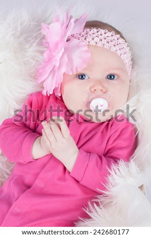 Portrait of sweet three months old baby girl in pink hairband with flower on a fluffy blanket in basket