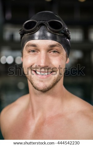 Portrait of swimmer wearing swimming goggles and cap by pool side - stock photo