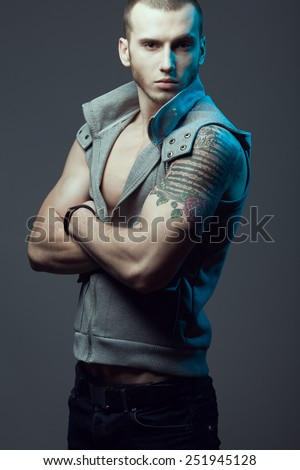 Portrait of tattooed brutal young model with short hair and bristle on face wearing sleeveless jacket, blue jeans and posing over gray background. Hipster style. Studio shot - stock photo