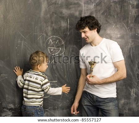 portrait of teacher and little student, father and son near blackboard