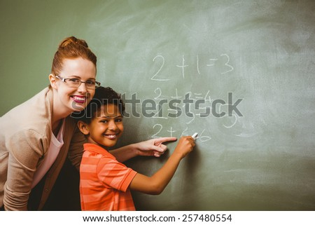 Portrait of teacher assisting little boy to write on blackboard in the classroom - stock photo