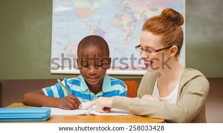 Portrait of teacher assisting little boy with homework in the classroom - stock photo