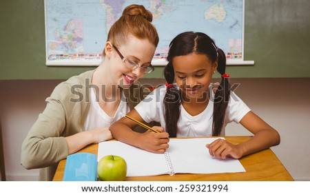 Portrait of teacher assisting little girl with homework in the classroom - stock photo