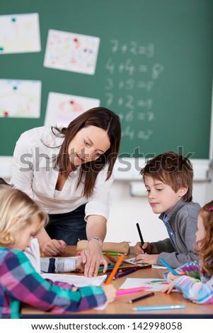 Portrait of teacher helping her pupils in art class - stock photo