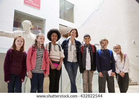 Portrait Of Teacher With Class Standing Inside Museum - stock photo
