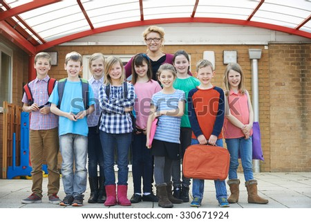 Portrait Of Teacher With Pupils In Playground - stock photo
