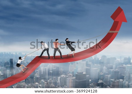 Portrait of teamwork try to raise arrow upward together above the city - stock photo