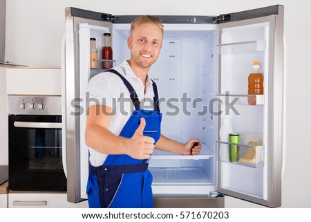 Portrait Of Technician Gesturing Thumbs Up In Front Of Refrigerator