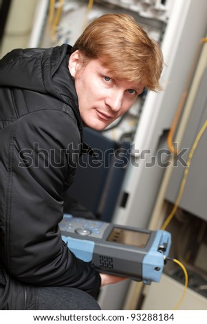 Portrait of technician with optical reflectometer at server room - stock photo