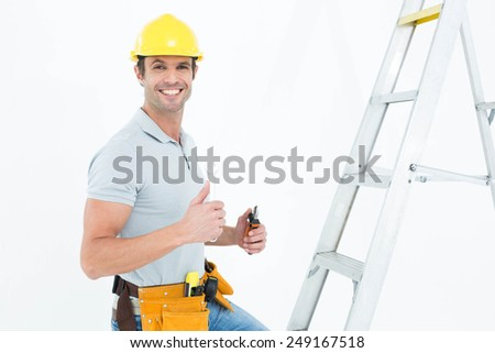 Portrait of technician with tools showing thumbs up sign in front of step ladder over white background