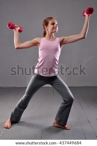 Portrait of teen age sportive girl exercising with dumbbells on grey background. Sport healthy lifestyle concept. Sporty childhood. Teenager child exercising with weights. - stock photo