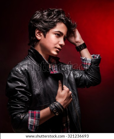 Portrait of teen boy wearing leather jacket and touching his stylish hairdo over dark red background, fashion for adolescents