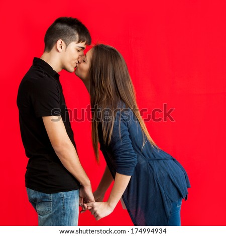 Portrait of Teen couple kissing against red background.  - stock photo