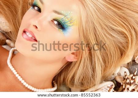 portrait of teen girl beauty cheerful enjoying like a mythology fairytale mermaid lying on shells with beautiful make-up - stock photo