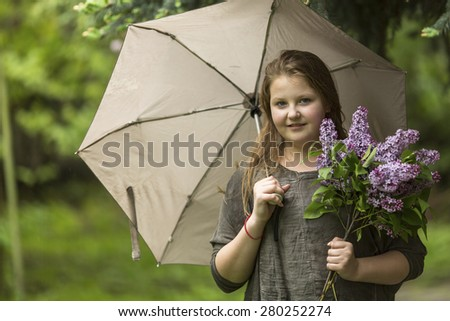 Portrait of teen girl with an umbrella and a bouquet of lilacs. - stock photo