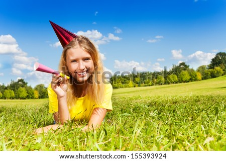 Portrait of teen little girl with noisemaker horn and birthday party cap laying outside with happy expression on sunny summer day - stock photo