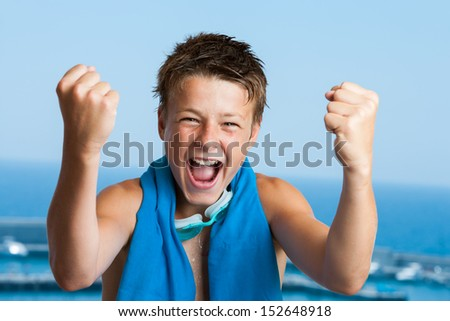 Portrait of teen swimmer with victorious face reaction. - stock photo