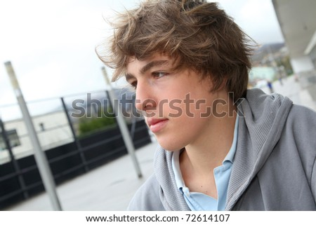 Portrait of teenage boy in front of school building
